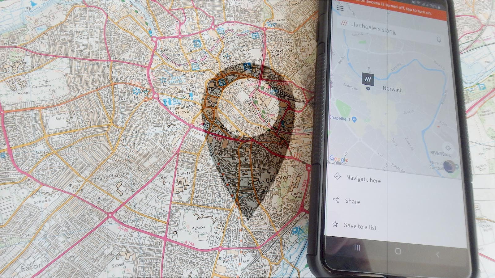 Image showing a 1:25000 OS map with a phone showing What 3 Words beside it, faded with a location symbol.